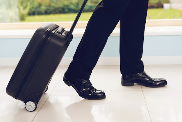 He carries a black suitcase behind him.