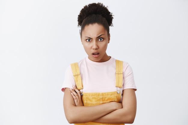 Ha fatto cosa. ritratto di donna africana di bell'aspetto sconvolta e confusa con le mani incrociate sul petto, sollevando le sopracciglia con espressione perplessa