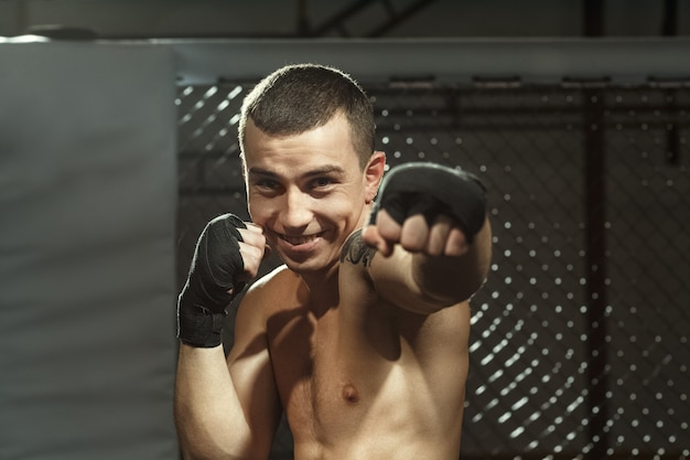 He fights with a smile on his face. young professional mma fighter smiling posing in a fighting cage