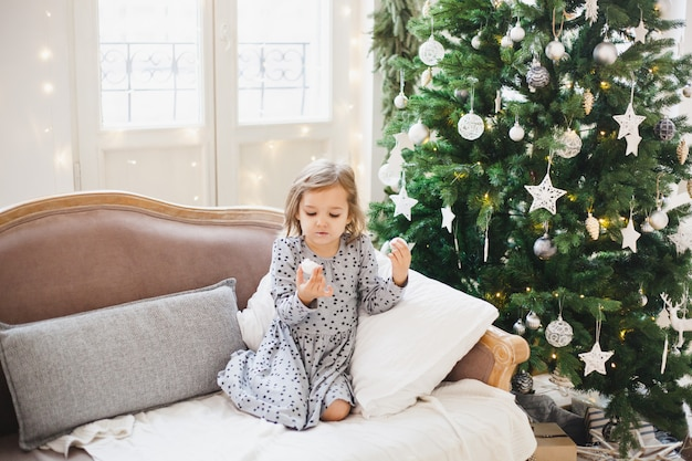 He girl is sitting on the couch and eating sweets next to the decorated christmas tree, the room is decorated for christmas