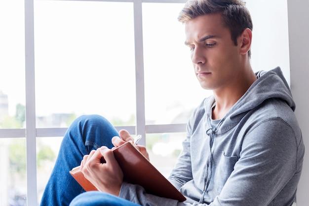 그는 창조적 인 영혼을 얻었습니다. 창틀에 앉아 메모장에 뭔가를 쓰고 있는 잘생긴 청년의 옆모습