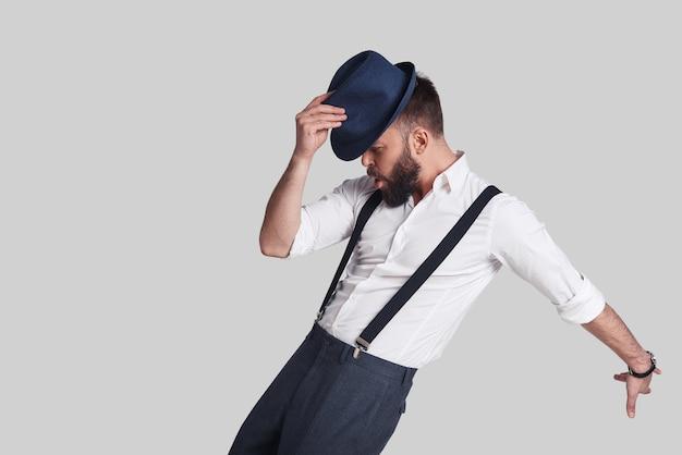 У него есть ходы. красивый молодой человек в подтяжках поправляет шляпу и гримасничает во время танца на сером фоне