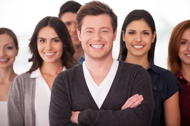 Он настоящий руководитель команды. уверенный молодой человек, скрестив руки и улыбаясь, пока группа людей стояла на заднем плане