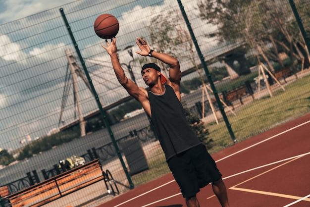 그는 승자입니다! 야외에서 농구를하는 동안 공을 던지는 스포츠 의류에 젊은 아프리카 남자