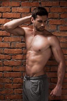 彼は完璧です。レンガの壁に立ってポーズをとってハンサムな若い筋肉の男