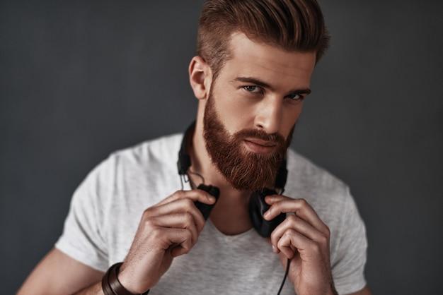 그는 당신의 마음을보고 있습니다. 그의 목에 헤드폰을 착용하고 회색 배경에 서있는 동안 카메라를보고 잘 생긴 젊은 남자