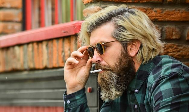 Он серьезен. брутальный зрелый хипстер курит сигарету. понятие вредных привычек. вредны для вашего здоровья. курить никотиновая зависимость. он заядлый курильщик. бородатый мужчина в очках расслабиться с сигаретой.