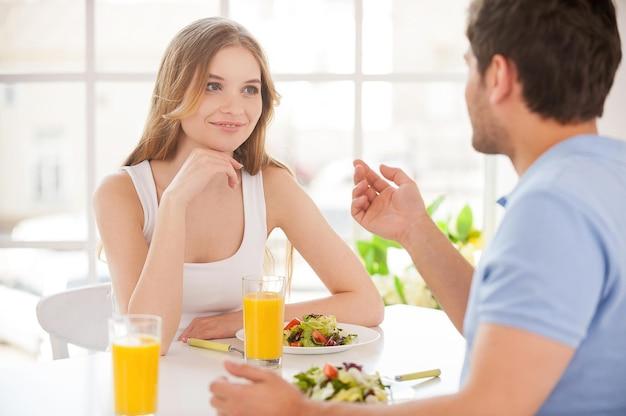 그는 정말 잘 생겼다! 아름 다운 젊은 부부는 함께 테이블에 앉아 아침 식사