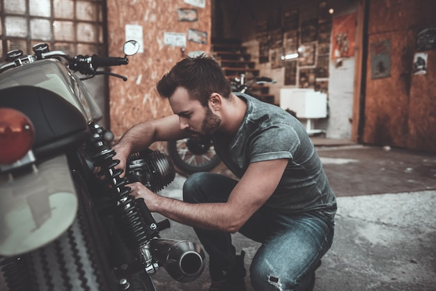 Он знает все о байках. уверенный молодой человек ремонтирует мотоцикл возле своего гаража