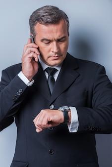 그는 시간이 돈이라는 것을 알고 있습니다. 회색 배경에 서서 시간을 확인하고 휴대폰으로 통화하는 정장 차림의 자신감 있는 성숙한 남자