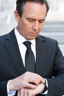 그는 시간이 돈이라는 것을 알고 있습니다. 야외에 서있는 동안 시간을 확인하는 formalwear에서 자신감 수석 남자