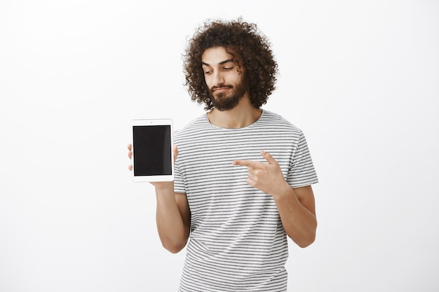 Sa quali gadget vale la pena acquistare. cliente maschio soddisfatto soddisfatto con barba e taglio di capelli alla moda in camicia a righe, indicando e guardando la tavoletta digitale con un leggero sorriso