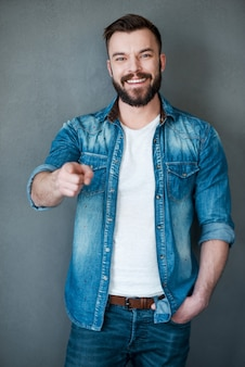 He knows what he wants!cheerful young man pointing you and smiling at camera while standing against grey background