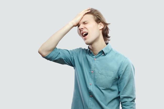 그는 모든 것을 잃었다. 파란색 캐주얼 셔츠에 서 있는 슬픈 잘생긴 장발 금발 청년의 초상화와 그의 실수 때문에 슬픈 것입니다. 밝은 회색 배경에 격리된 실내 스튜디오 촬영.