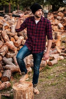 彼は木を扱うのが大好きです。彼の肩に斧を運び、屋外に立っている間目をそらしているハンサムな若い森の長さ