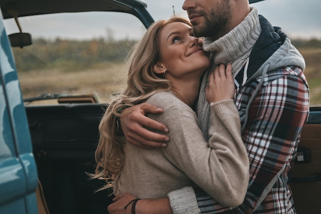 He means everything to her.  beautiful young couple embracing and smiling while standing outdoors near the retro style car