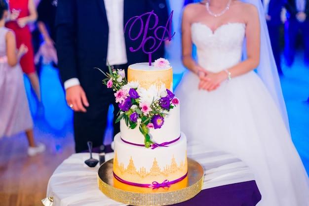 그는 신혼 부부가 손을 잡고 식당 홀에서 웨딩 케이크 손님을 봅니다.