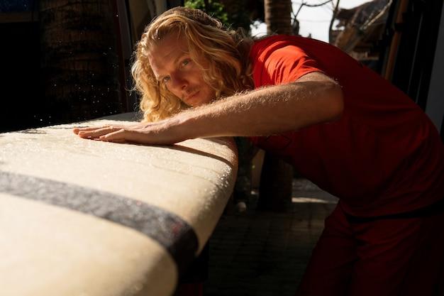 Il surfista lava la sua tavola con l'acqua. bali