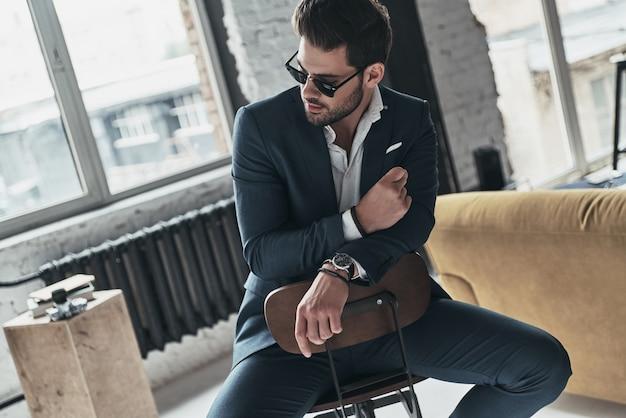 彼はあなたの心を溶かします。完全なスーツとスツールに座っている間目をそらしている眼鏡のハンサムな若い男