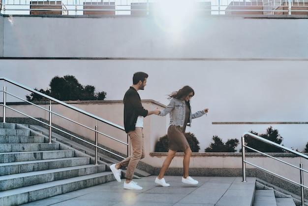 그는 그녀를 절대 보내지 않을 것입니다. 잘 생긴 남자와 손을 잡고 젊은 매력적인 여자의 전체 길이