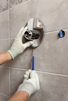 He workes hands install the tube of the built in shower faucet