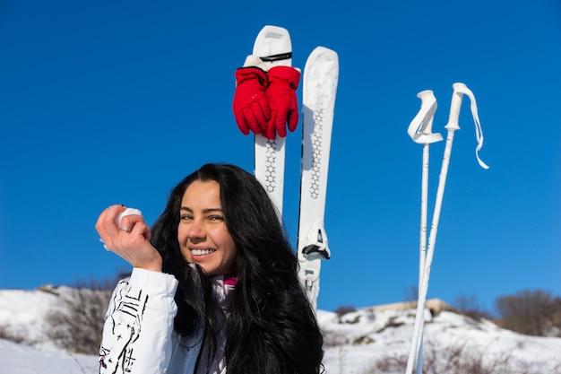 Голова и плечи откровенный портрет молодой женщины с длинными темными волосами, которая отдыхает от катания на лыжах, чтобы съесть яблоко на снежном склоне горы с лыжами и палками поблизости в солнечный день с теплым солнцем