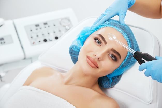 미용 클리닉에서 파란색 모자에 소파에 누워있는 여자의 머리와 어깨. 그녀의 얼굴 가까이 darsonvales를 들고 의사