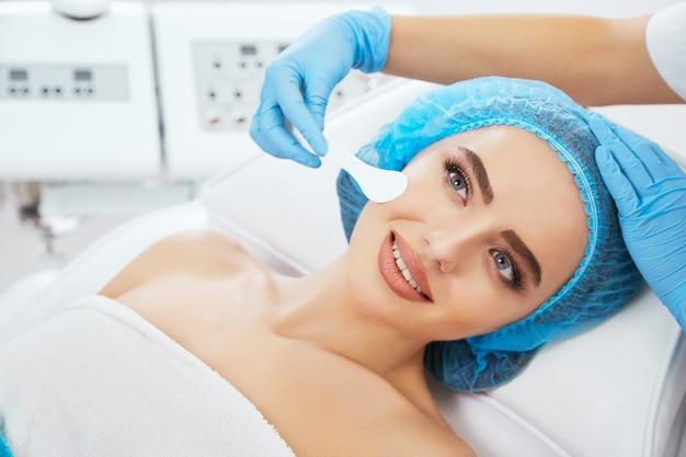 미용 클리닉에서 파란색 모자에 소파에 누워, 옆으로보고 웃 고 여자의 머리와 어깨. 그녀의 얼굴 가까이 uno 숟가락을 들고 의사