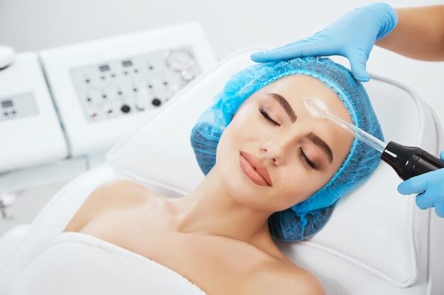 닫힌 된 눈과 미소와 미용 클리닉에서 파란색 모자에 소파에 누워 여자의 머리와 어깨. 그녀의 얼굴 가까이 darsonvales를 들고 의사