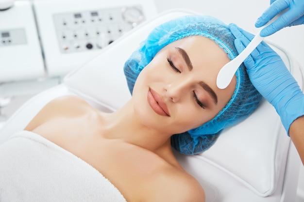 닫힌 된 눈과 미소와 미용 클리닉에서 파란색 모자에 소파에 누워 여자의 머리와 어깨. 그녀의 얼굴 가까이 uno 숟가락을 들고 의사