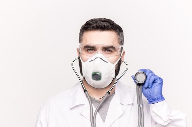 ホワイトコート、レスピレーター、手袋、眼鏡をかけた若い臨床医の頭と肩が病院で聴診器で病気の患者を診察している