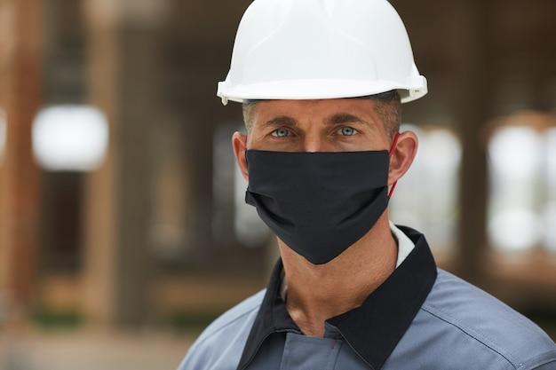 마스크를 쓰고 산업 현장에서 작업하는 동안 성숙한 노동자의 머리와 어깨 초상화,
