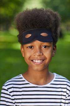 ハロウィーンの盗賊の衣装を着て、屋外でポーズをとっている間、笑顔のアフリカ系アメリカ人の少年の頭と肩の肖像画