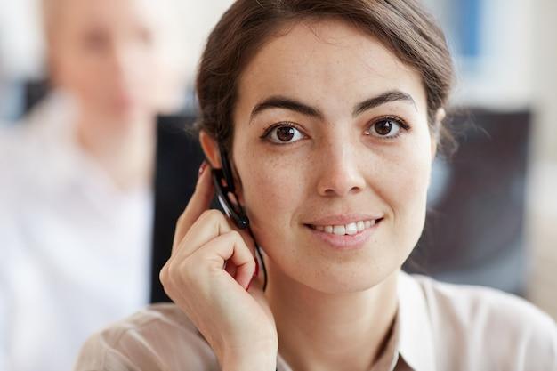 Голова и плечи портрет улыбающейся молодой женщины в гарнитуре и глядя во время работы в колл-центре службы поддержки