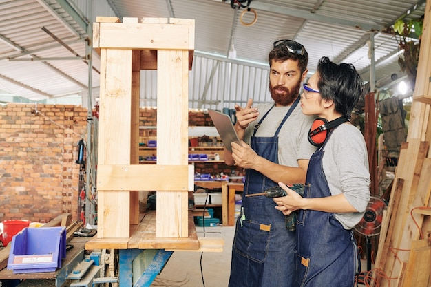 Главный плотник с планшетным компьютером проверяет деревянную подставку, сделанную его учеником в мастерской
