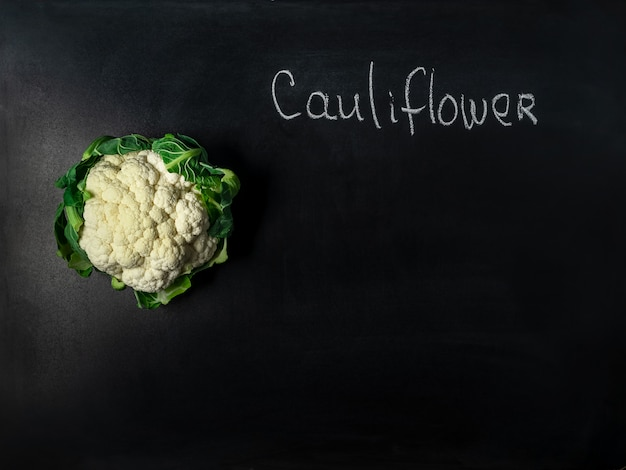 Head of cauliflower on black board with incription