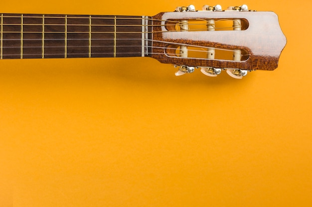 Head of classical acoustic guitar on yellow background