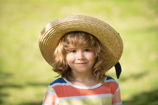 頭をクローズアップ。麦わら帽子をかぶった子供のヘッドショットをクローズアップ。子供の顔、小さな男の子の肖像画。