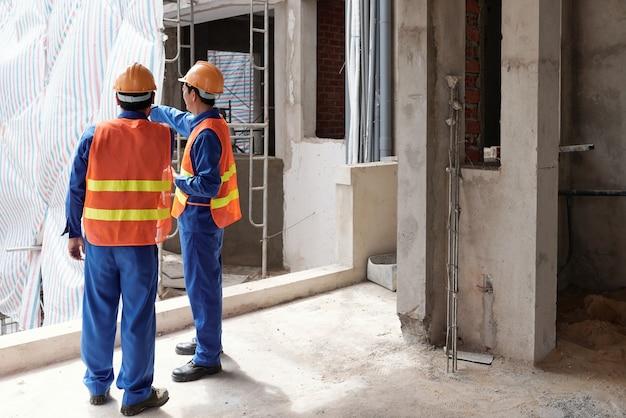 建設マネージャーに現場を示し、彼のチームがどのような変化をもたらすかを説明する元請業者...