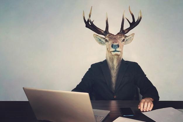 Голова оленя. понятие о безмозглости и глупости власти или правительства. начальник - дурак, тупой предприниматель, сидящий за столом с ноутбуком, телефоном и документами, неразумный, бездумный