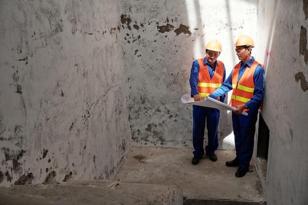 建設中の建物の中に立って話し合っているヘルメットをかぶったヘッドエンジニアと請負業者...