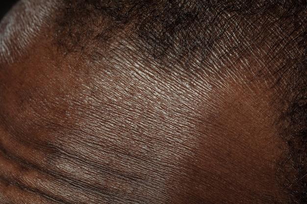 頭、顔。人間の肌の詳細な質感。若いアフリカ系アメリカ人の男性の体のクローズアップショット。スキンケア、ボディケア、ヘルスケア、衛生、医学の概念。美しさと手入れの行き届いたように見えます。皮膚科。