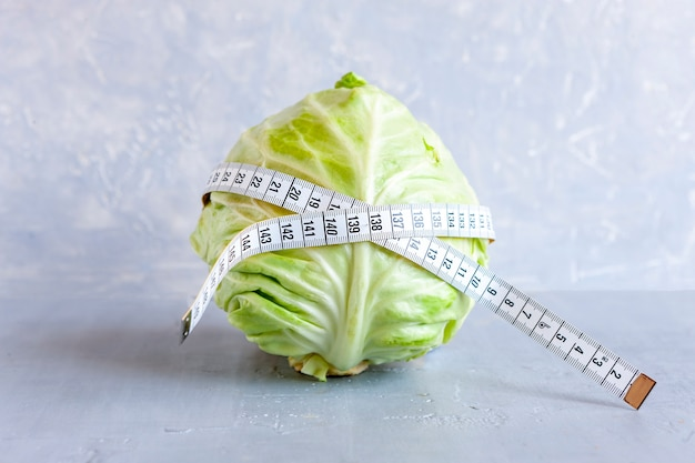 A head of fresh cabbage and a centimeter in the waist. intermittent fasting concept, ketogenic diet, weight loss