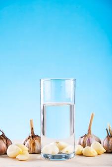 testa di aglio in un bicchiere d'acqua sull'acqua dell'aglio blu, prevenzione delle malattie