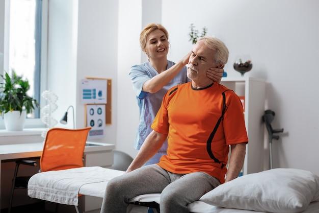 머리 마사지. 그의 머리를 마사지하는 동안 그녀의 환자 뒤에 서있는 즐거운 친절 한 간호사