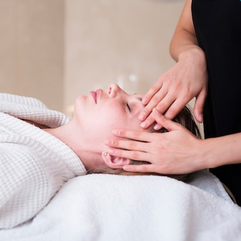 Head massage technique on woman at spa