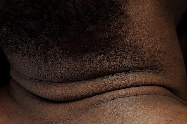 頭、首。人間の肌の詳細な質感。若いアフリカ系アメリカ人の男性の体のクローズアップショット。スキンケア、ボディケア、ヘルスケア、衛生、医学の概念。美しさと手入れの行き届いたように見えます。皮膚科。