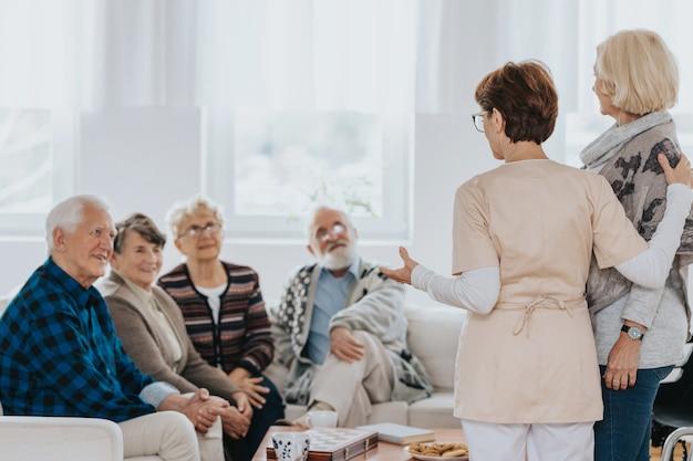 Старшая медсестра разговаривает с новыми пациентами, сидящими на диване в доме престарелых