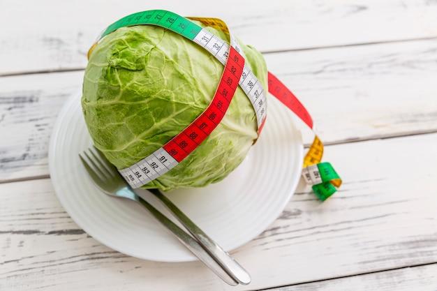 木製の背景のプレートに巻尺とキャベツの頭。食事と体重管理。上面図。