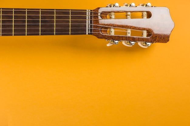 Глава классической акустической гитары на желтом фоне